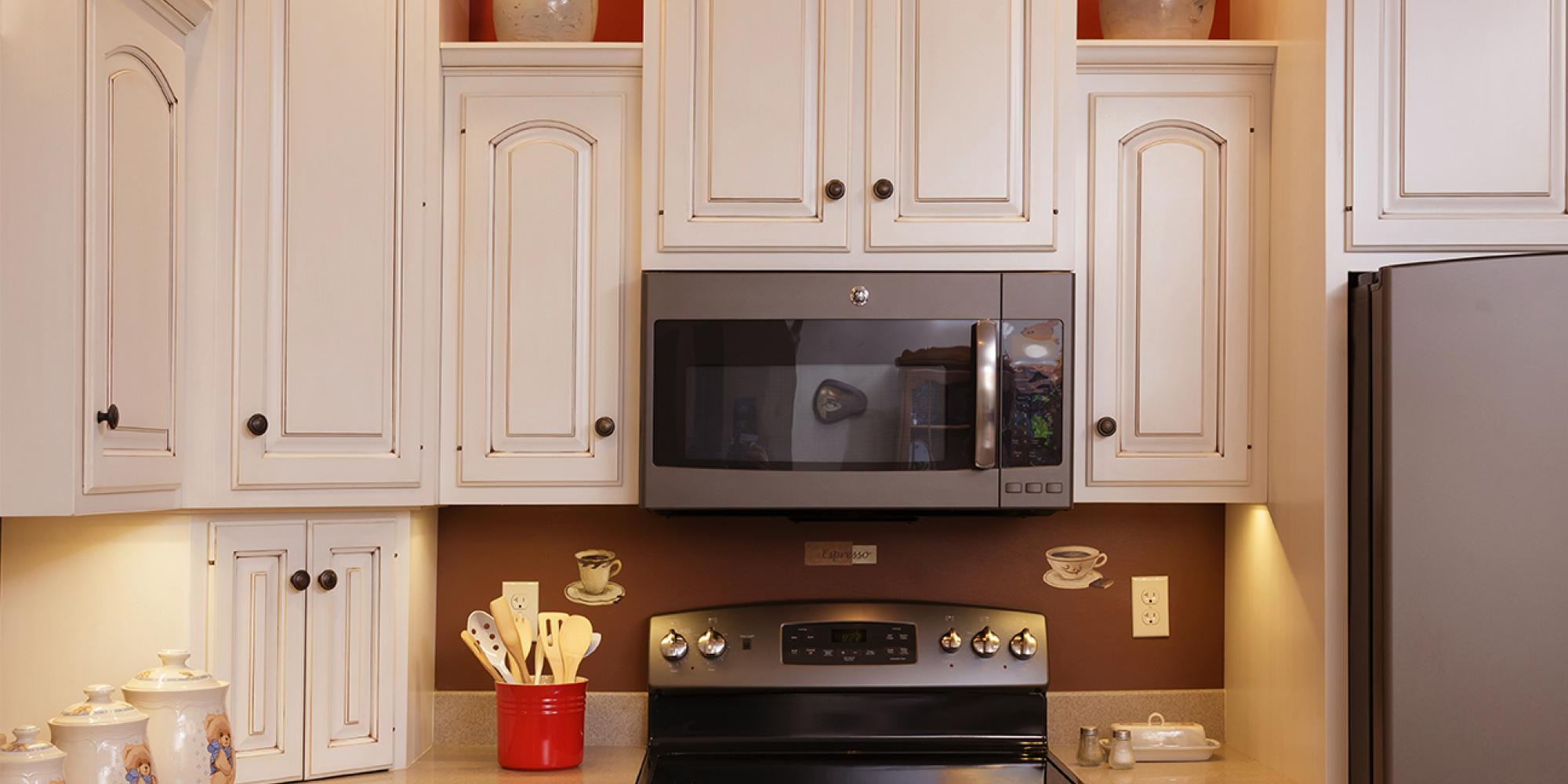 Solid wood kitchen in Liverpool, PA, showing appliance garage and cupboards installed around the microwave, color white with brown glaze