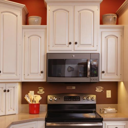 Hardwood white glazed corner kitchen cabinets and cabinets above and beside the microwave in Liverpool, PA