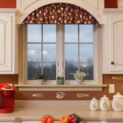 Decorative arch over kitchen window and pull out cutting board beneath the countertop