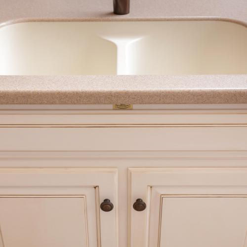 Kitchen sink and white painted cabinet with brown glaze
