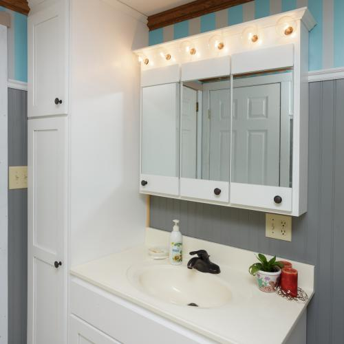 White bathroom vanity, floor to ceiling linen closet, and lighted medicine cabinet with mirrors on the doors