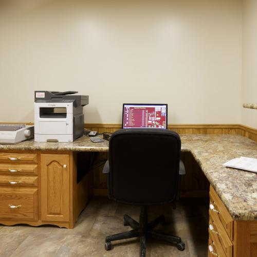 Corner office desk space with solid wood cabinets and drawers
