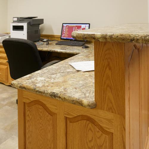Transaction counter and receptionist's workspace with granite design top and hardwood cabinets in Liverpool, Pennsylvania