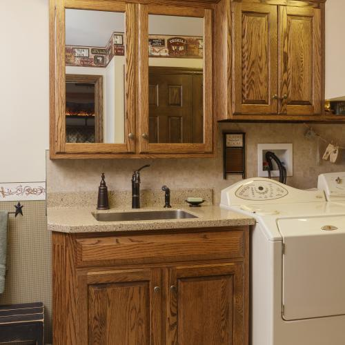 Laundry room sink with stained oak vanity, medicine cabinets, and cabinets above the dryer