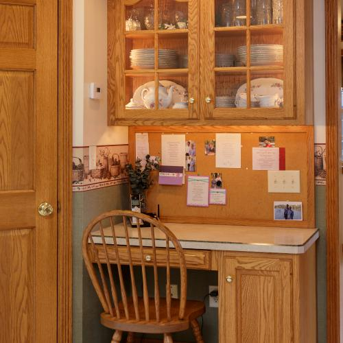 Oak wood desk that fits in a kitchen corner with glass door cabinet above